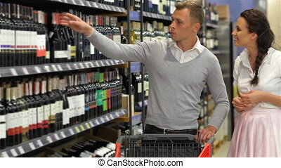 Smiling casual couple looking at wine bottle in supermarket.