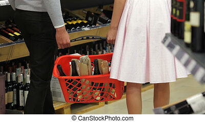 Close-up of couple looking at wine bottle in supermarket.