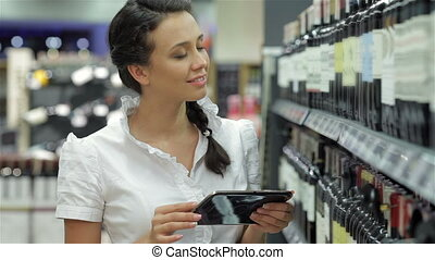 The girl chooses wine with a tablet - Woman in the store...