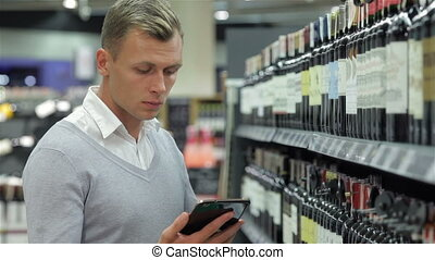 The male chooses wine with a tablet - Male in the store...