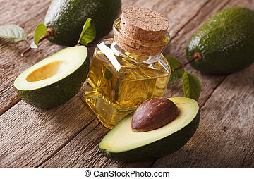 natural avocado oil in a bottle on a wooden table close-up,...