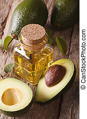 Useful avocado oil in a bottle on a wooden table close-up,...