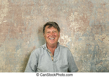 portrait of senior man in front of grungy old wall in a...