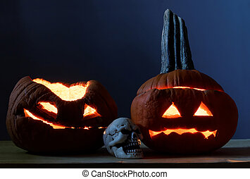 Two halloween pumpkins and scull
