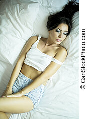 Pretty young woman relaxing in the bed