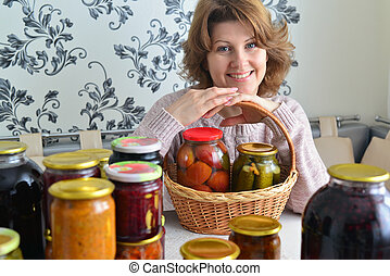 housewife with home canned vegetables in room - housewife...