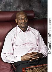 Serene contented guy sitting on sofa