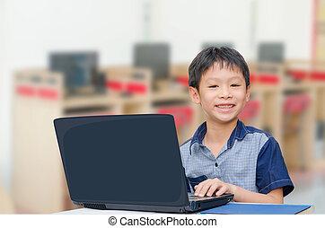 boy using notebook computer - Little Asian boy using...