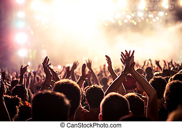 This party's on fire - Audience with hands raised at a music...