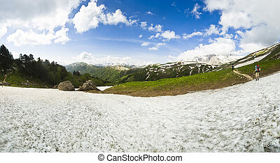 panorama of summer snow mountains with hikers on the path -...