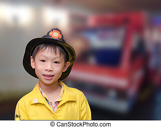Little Asian boy in firefighter uniform in front of truck