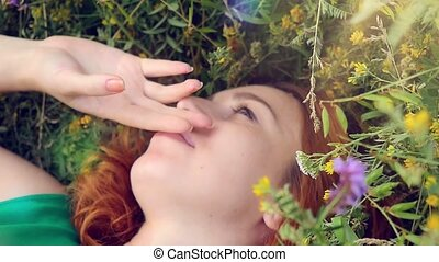 dreamy attractive young red-haired woman with flowers relaxing outside on a meadow full of flowers and smiles