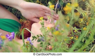 pensive dreamy attractive young red-haired woman with flowers relaxing outside on a meadow full of flowers.