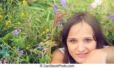 Smiles beautiful young woman lays down on a flower meadow. relaxing on grass