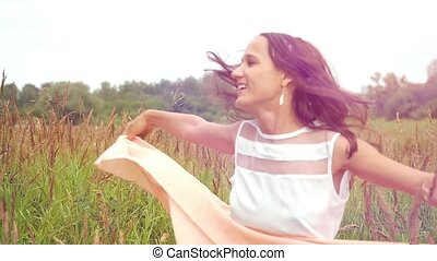 Young happy beautiful woman runs on a flower meadow, spinning and laughing at sunset time