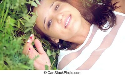 young cute summer brunette girl  lays down in  flower meadow  and smelling the flowers thoughtfully romantic