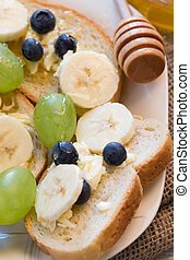 Bread toast with honey and banana on plate