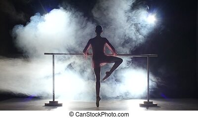 little ballerina that makes stretching the legs near the barre. smoke