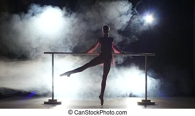 Graceful ballerina that makes stretching the legs near the barre. smoke