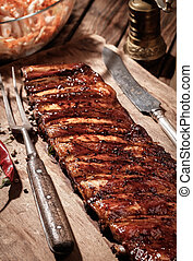 Delicious BBQ ribs with coleslaw on wooden table