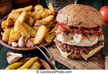 Tasty beefburger with bacon, fried egg and mushrooms and...
