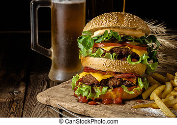 Delicious beef burger with chips and beer on wooden table. -...