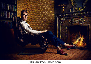 by a fireplace - Elegant handsome young man sitting by the...