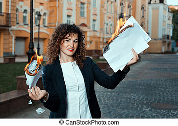 Girl is holding the documents that burn. She is in the city.