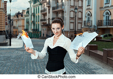 Girl with joy on her face burn documents. On the streets of...