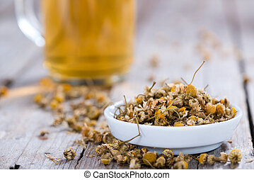 Portion of dried Camomile (close-up shot) on an old wooden...