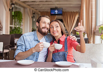 Handsome man and pretty woman in cafeteria - Cheerful young...