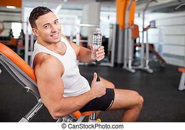 Handsome young male athlete is resting after training -...