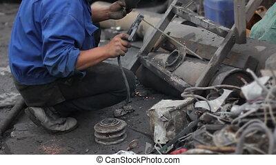 Worker welding the item of conveyor - Worker repairing the...
