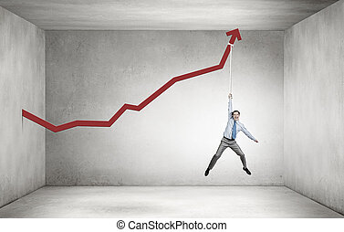 Growing graph - Young businessman hanging on increasing red...