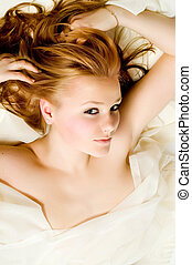 The beautiful young girl lays in a fabric