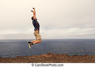 Success or win concept - joyful man jumping