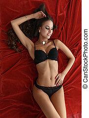 Sexy model in lingerie lying on velvet bedsheets - Image of...