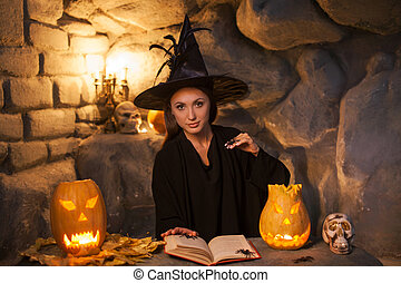 Cheerful young witch is conjuring in Nut-Crack Night -...