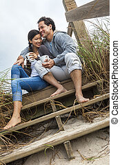 Asian Man Woman Couple Drinking Coffee on Beach Steps -...