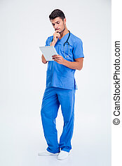 Thoughtful male doctor holding tablet compute - Full length...