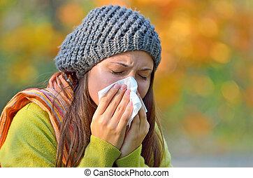 Girl sneezing in tissue. - Girl in fall autumn park sneezing...