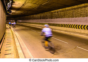 Motion blur of cyclist in underground road.