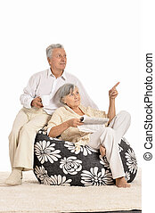 Senior couple reading at home sitting on black armchairs