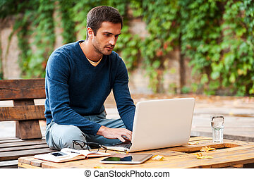 Business on fresh air Confident young man working on laptop...