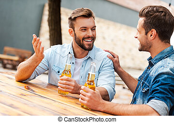Beer time. Two cheerful young men talking to each other and holding bottles with beer while standing outdoors