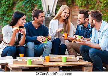 Quality time with friends. Group of joyful young people talking to each other and eating pizza while sitting outdoors