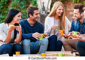 Spending good time with friends. Group of cheerful young people talking to each other and eating pizza while sitting outdoors