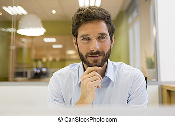Portrait of handsome bearded man in office. looking camera -...