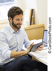 Handsome casual businessman working on computer in modern...