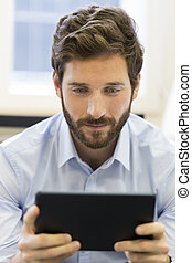 Casual businessman working on tablet computer in office -...
